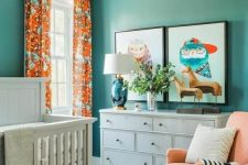 a bold mid-century modern nursery with green walls, white, grey and peachy furniture, bright artworks, colorful printed textiles
