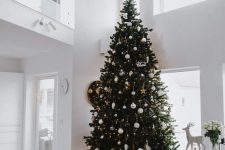 a bold modern Christmas tree decorated with lights, white, metallic ornaments of various shapes and with a star topper