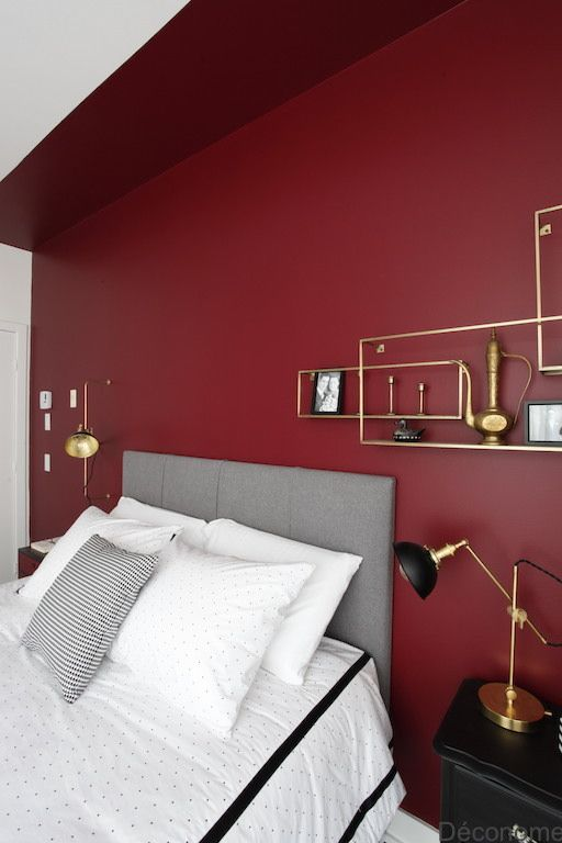 a bold modern bedroom with a burgundy accent wall, a grey bed, black nightstands and touches of gold or a chic look