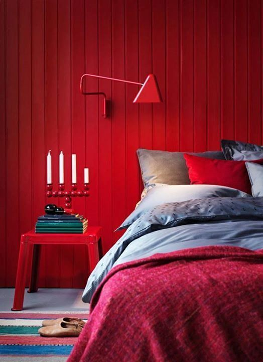 a bold modern bedroom with a red accent wall,grey, red and burgundy bedding, a red nightstand and a catchy candelabra is a wow space
