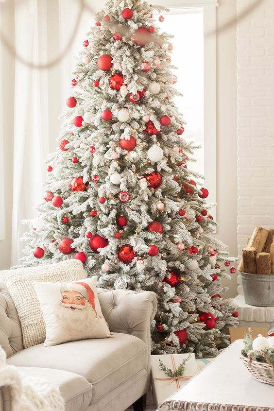 a bold modern flocked Christmas tree with red and white ornaments of various sizes is a chic idea