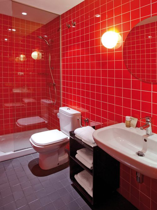 a bold modern red bathroom with medium size square tiles, white appliances, a round mirror, lights and white towels