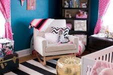 a bold nursery with navy walls, a striped rug, a gold ottoman, pink and white textiles and a bright gallery wall
