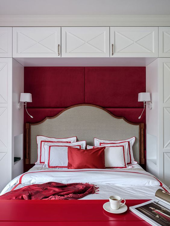 a bold red and white bedroom with a storage unit in white, a bed integrated into a niche, a red bench and red bedding
