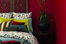 a bold red bedroom with a unique carved wooden screen as a headboard, printed bedding, a beautiful pendant lamp and some greenery in a pot