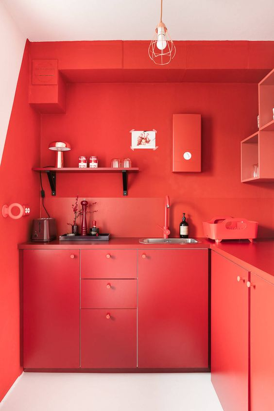 a bold red solid kitchen with chic cabinets, shelves, backsplashes and countertops is completely red and statement-like