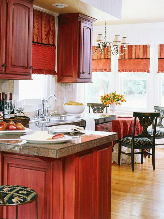 a bold red vintage kitchen with pretty cabinets, stone countertops and dark chairs and stools looks very refined and cool