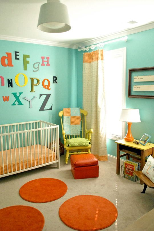 a bold vintage nursery with turquoise walls, a yellow chair and a nightstand, orange rugs, bold textiles and bright letters