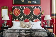 a bright and catchy bedroom with a bold red accent wall, a bed with a unique patterned headboard, refined nightstands and lamps