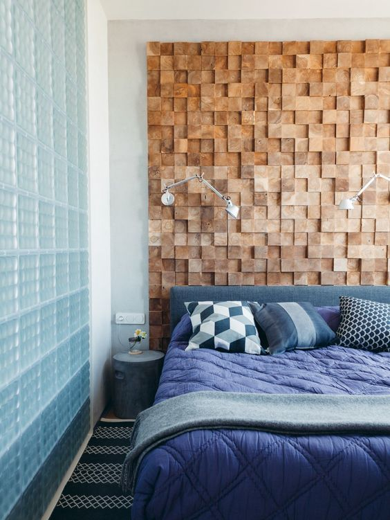 a bright bedroom with a wood square accent wall, an upholstered bed, bright blue bedding and geometric pillows is amazing