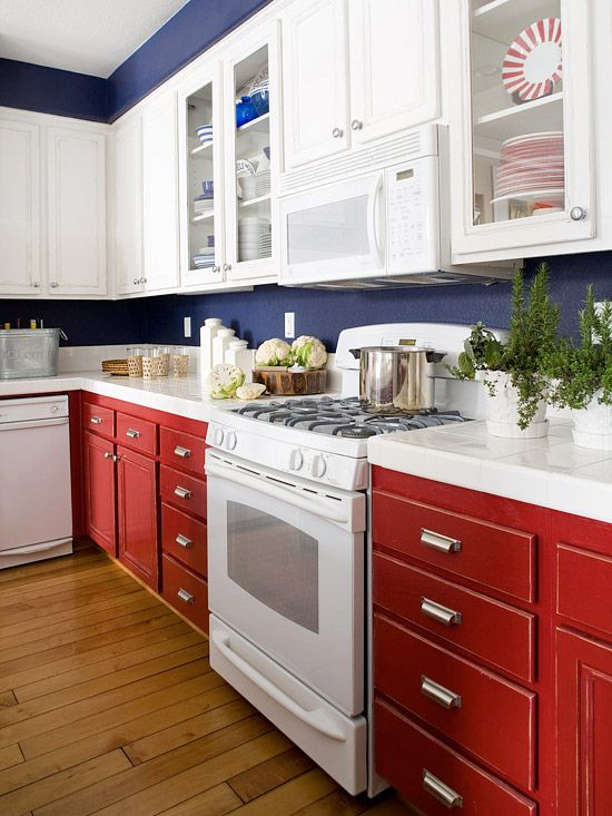 a bright kitchen with white and red cabinets, navy walls and white stone countertops is a stylish idea with bright shades