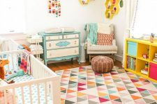 a bright mid-century modern nursery with a yellow shelf, a turquoise dresser, colorful bedding and a rug, bold honeycomb shelves