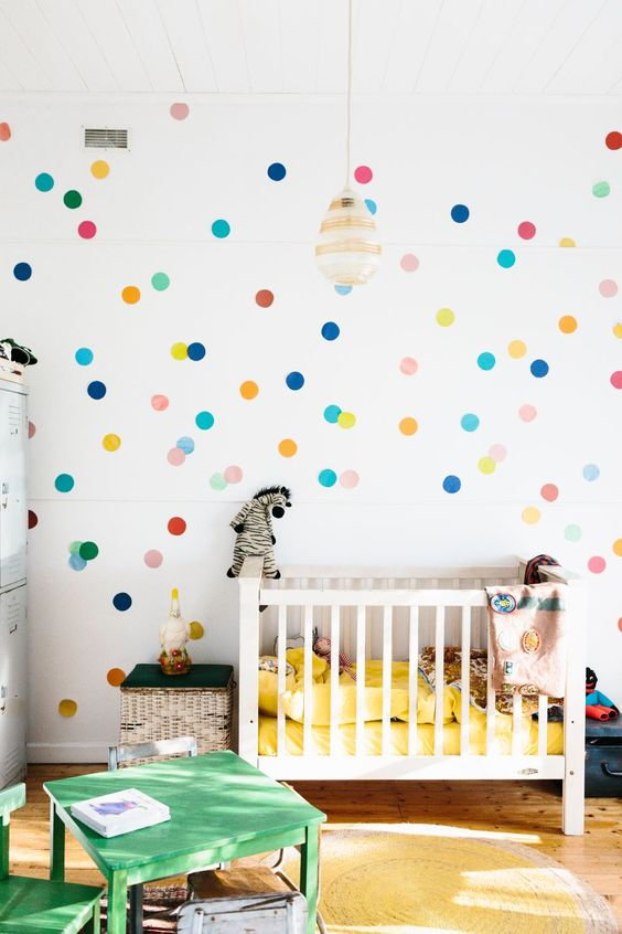 a bright modern nursery with a colorful polka dot wall, bright yellow bedding, green furniture and fun toys