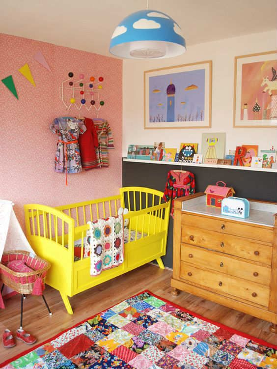 a bright nursery with a pink printed wall, a color block wall, a yellow crib, a bold patchwork rug, lots of colorful books and artworks