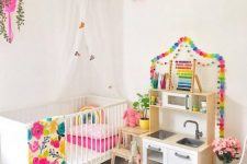 a bright nursery with all white everything spruced up with bold linens, rugs and garlands looks amazing