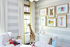 a bright nursery with striped walls, a super colorful rug, neutral textiles, a fun and bright gallery wall with framed art