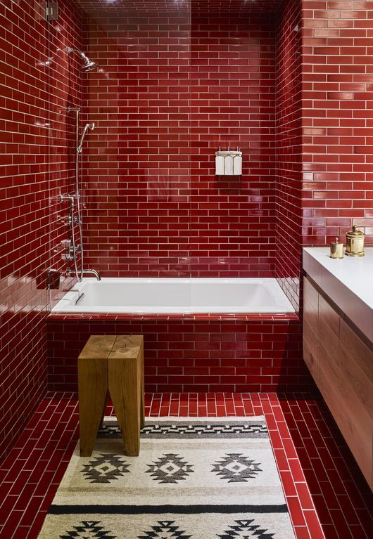 a bright red bathroom clad with subway tiles, with a floatign wooden vanity, white appliances, a wooden stool and a boho rug