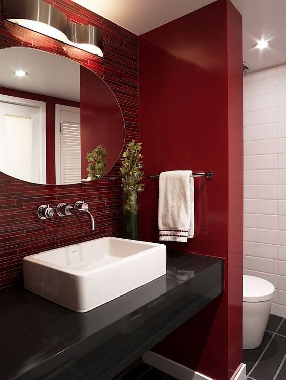 a bright red bathroom with catchy tiles on the wall and a space divider, white appliances and lights here and there