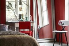 a bright red bedroom with neutral vintage furniture, an oversized mirror, a red chair and a floral one, a red rug is super bold