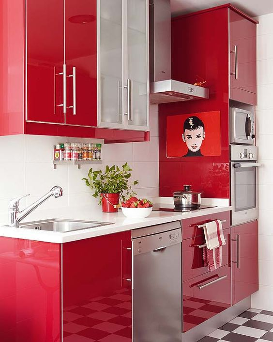 a bright red contemporary kitchen with a white backsplash and metal appliances looks laconic, bold and stylish