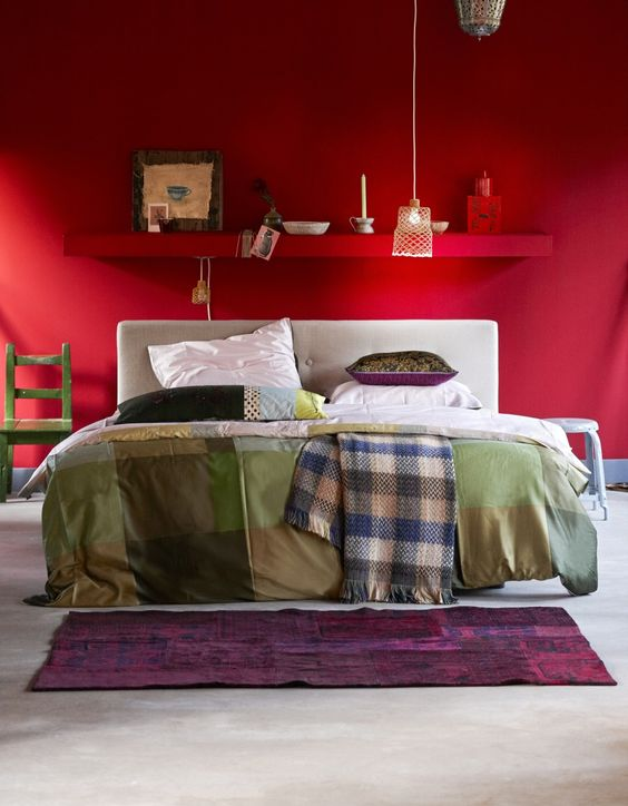 a bright red eclectic bedorom with a shelf over the bed, a white bed with printed bedding, accessories and decor and a pendant lamp