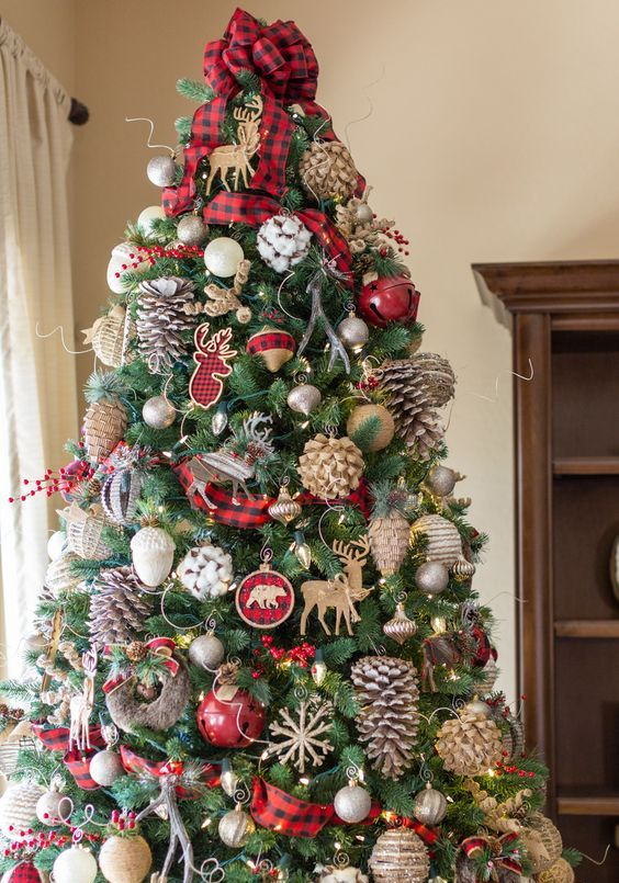 a bright rustic Christmas tree with plaid ribbons, bows and ornaments, large pinecones, bells and pretty plywood deer ornaments