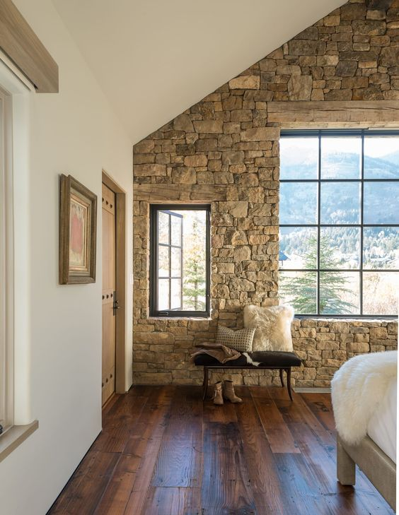 a cabin bedroom with a stone accent wall, an attic roof, modern furniture and a gorgeous mountain view is very welcoming