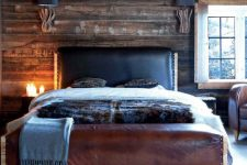 a cabin-inspired bedroom with a dark stained wooden wall, a leather bed and a rug that imitates wood slices
