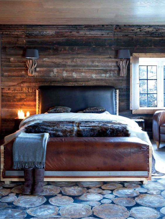 a cabin inspired bedroom with a dark stained wooden wall, a leather bed and a rug that imitates wood slices