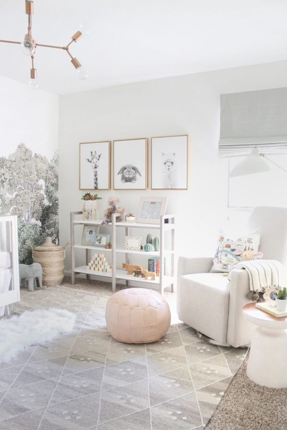 a catchy neutral nursery in white and grey, with a printed wall, a gallery wall with artworks, a shelving unit, white furniture, a pink ottoman and grey textiles