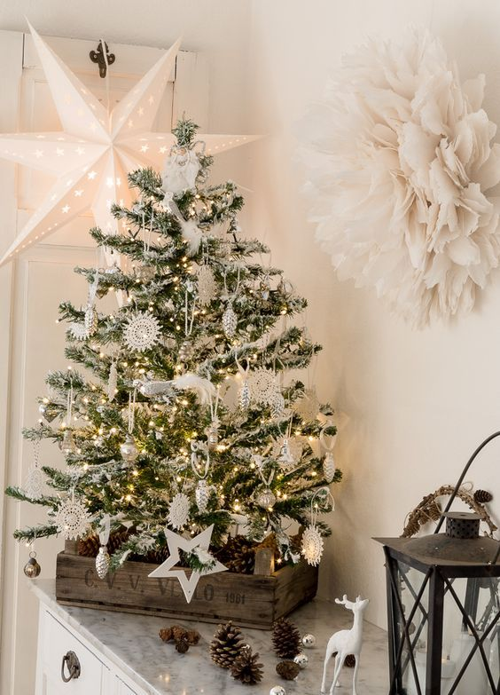 a charming vintage tabletop Christmas tree with lights, white and silver ornaments, lacey snowflakes and lots of pinecones in the crate