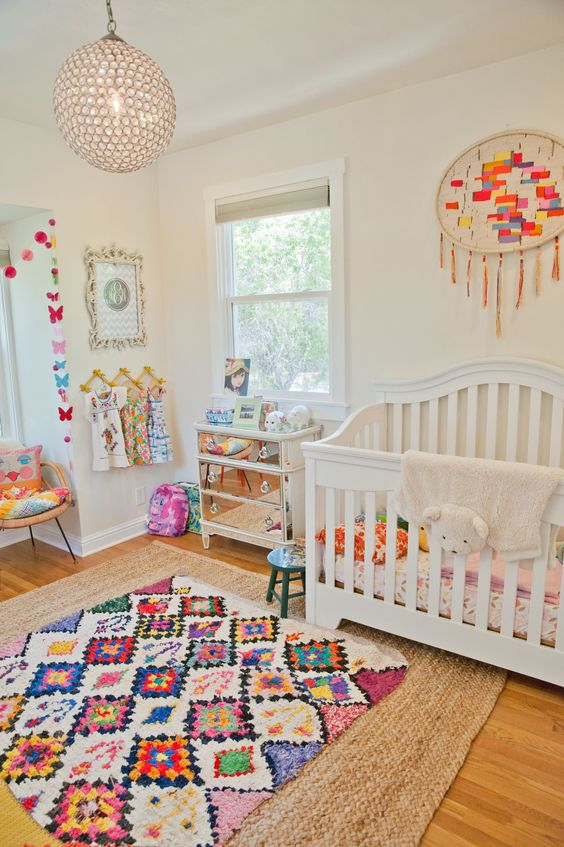 a cheerful nursery done in neutrals, with a mirror dresser, colorful bedding, rugs and garlands is very fun