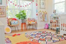 a cheerful nursery with bold layered rugs, garlands, pillows, bedding and neutral furniture and a mirror dresser