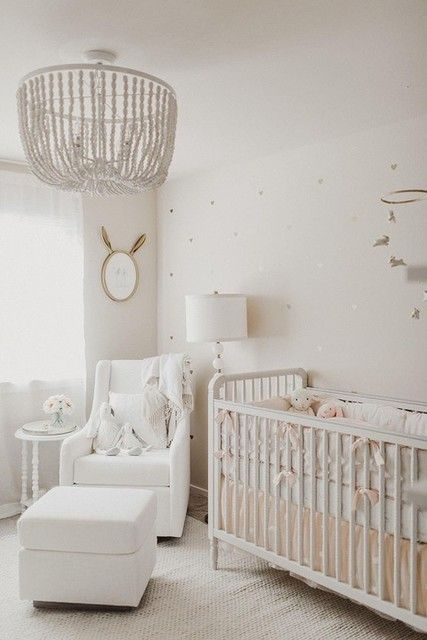 a chic and cozy white nursery with a heart wall, white vintage furniture, a beaded chandelier and a mobile and a mirror