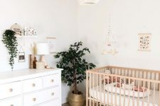 a chic and neutral nursery with white and neutral wooden furniture, a woven chandelier, statement plants and some artworks