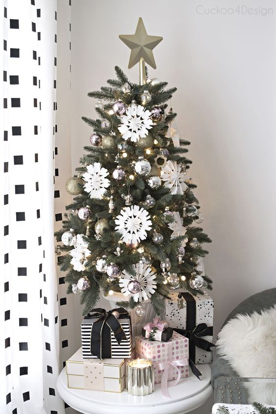a chic and shiny tabletop Christmas tree with lights, silver and gold glitter ornaments, white paper snowflakes and a star topper