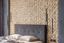 a chic contemporary bedroom with a wooden square accent wall, dark walls and furniture, catchy pendant lamps