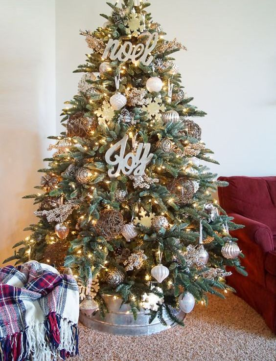 a chic farmhouse Christmas tree with lights, calligraphy, metallic ornaments, pinecones, snowflakes and with a metal base