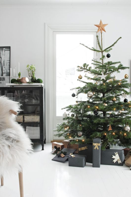 a chic modern Christmas tree with lights, gold, black and silver ornaments plus a star topper and lots of gifts
