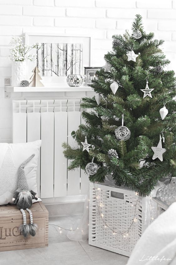 a chic modern Christmas tree with white and silver ornaments of creative shapes, in a white basket and with lights is cool