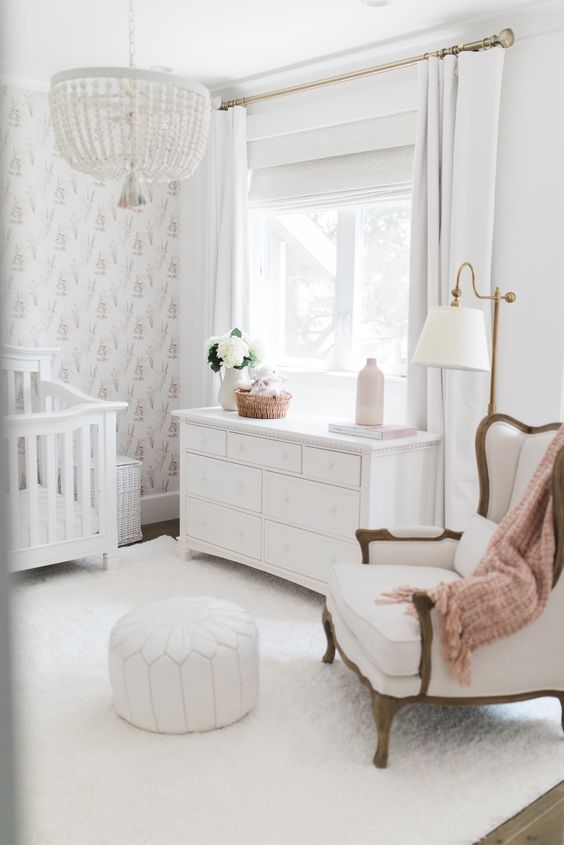 a chic neutral nursery with a printed statement wall, a chair, white vintage furniture, a beaded chandelier and a white leather ottoman