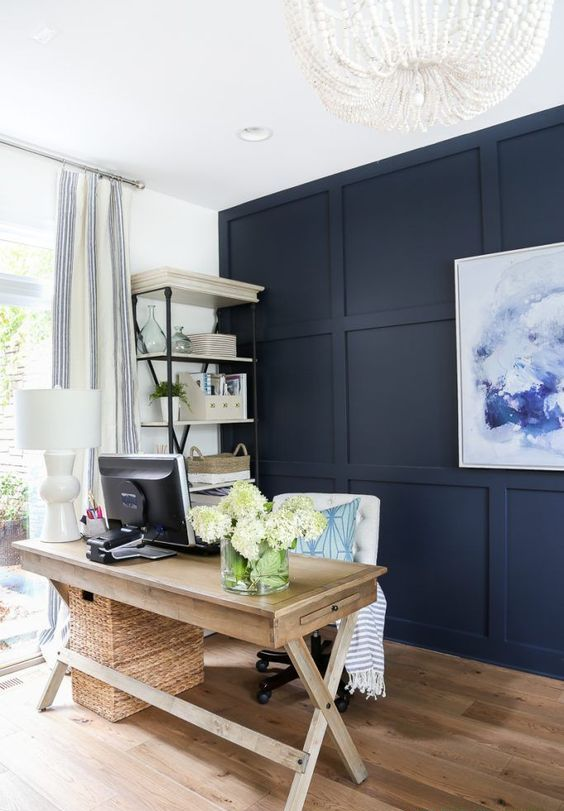 a chic rustic home office with a navy paneled wall, a wooden trestle desk, a basket, a white chair and a shelving unit plus a beaded chandelier