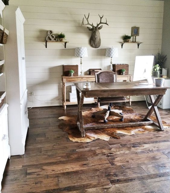 a chic rustic home office with a wooden trestle desk, a wooden console, lamps, shelves and some vintage table lamps