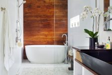 a cognac-colored wood accent wall to bring a cozy and eye-catching touch and contrast the neutral tiles around