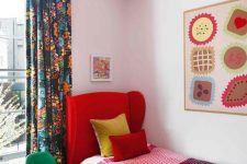 a colorful guest bedroom with a red upholstered bed, colorful bedding, a bright artwork, a white and red pendant lamp and a green chair