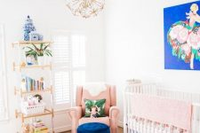 a colorful nursery with a bold artwork, a navy ottoman, a bright floral rug and bedding, a pink chair and bedding plus touches of gold