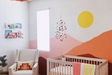 a colorful nursery with bold mountains painted, colorful bedding and rugs, a bold ombre tassel chandelier and bright books