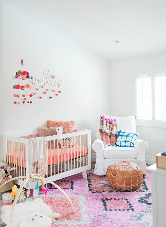 a colorful nursery with white furniture and bold bedding, rugs, pillows and colorful pompoms on the wall