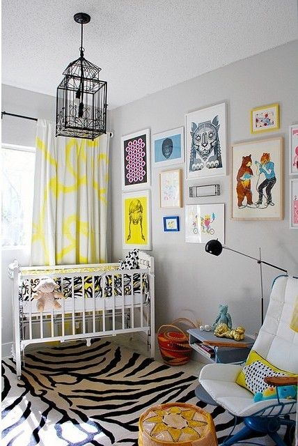 a colorful nursery with white furniture, bright textiles, a gallery wall with colorful artworks and a cage chandelier