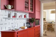 a colorful pink and red kitchen with sleek cabinets with no handles and a catchy patterned white tile backsplash